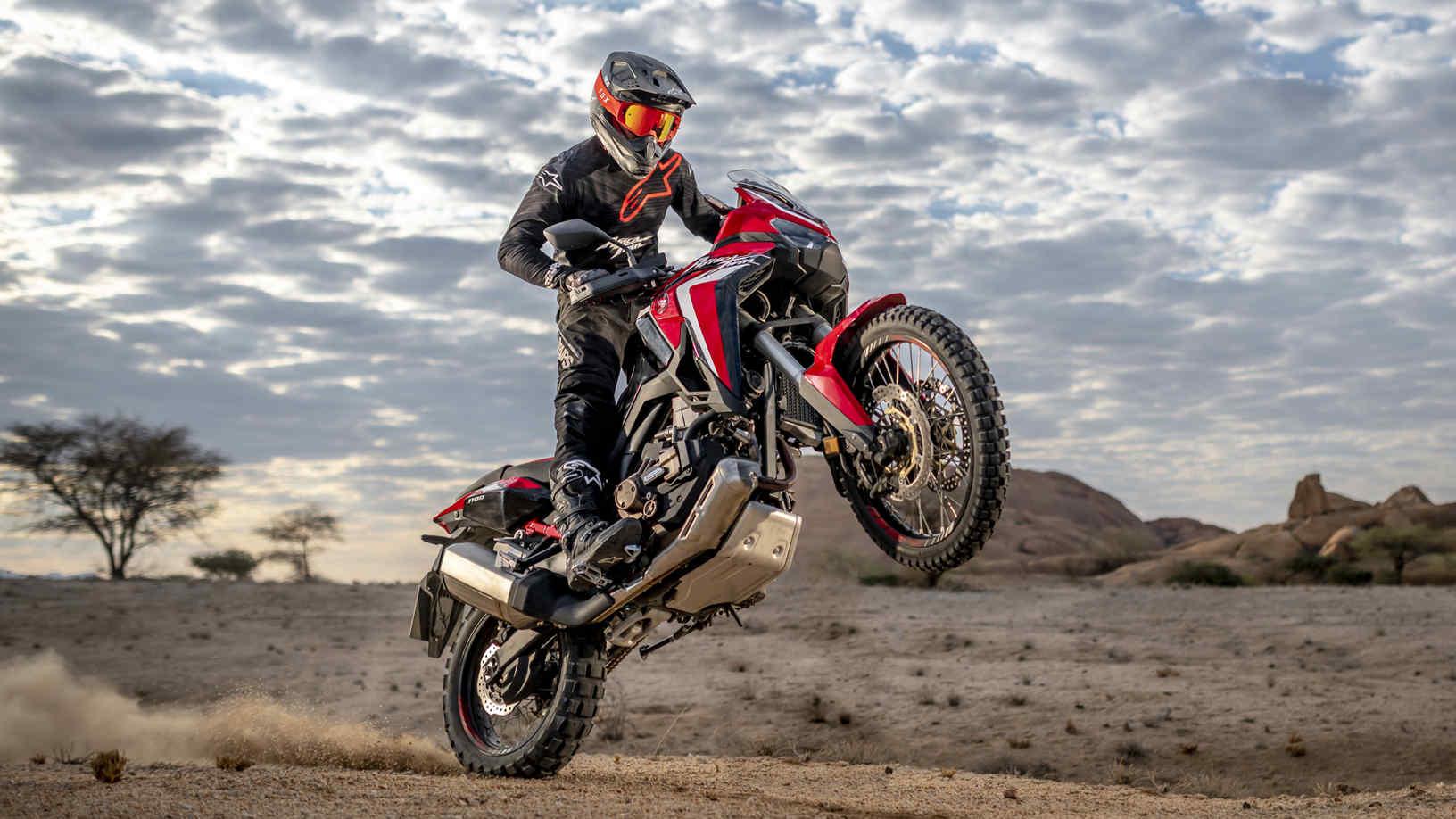 Honda Africa Twin, přední pravý poloprofil, jízda na zadním kole pouštní krajinou