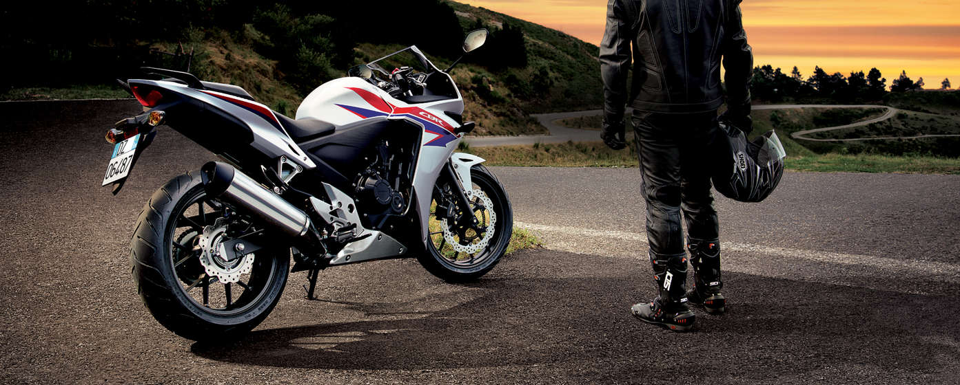 Honda cbr500r, rear three-quarter view with rider standing to its right side on rural location.