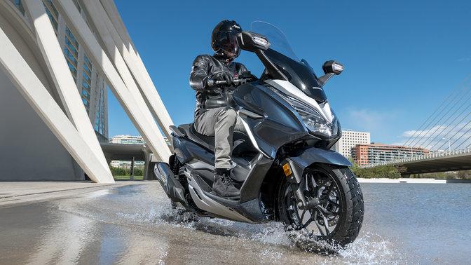 Pohled na přední tři čtvrtiny motocyklu Honda Forza 300 jedoucího vodou