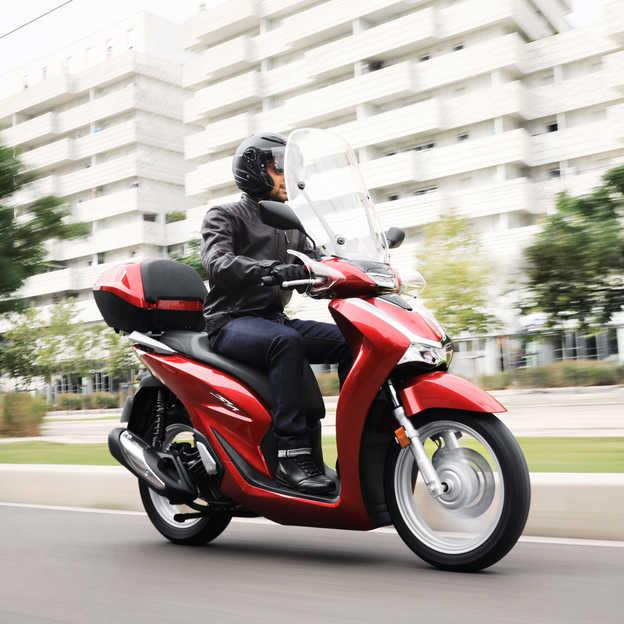 Honda SH125i, pravý přední poloprofil s jezdcem ve městě