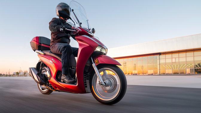 Honda SH350i, pravý přední poloprofil, sjezdcem, na silnici, červený motocykl