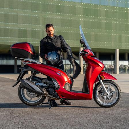 Honda SH350i, muž stojící vedle skútru, pohled zezadu, červený motocykl