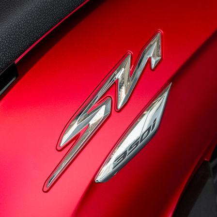 Honda SH350i, záběr na logo SH, červený motocykl