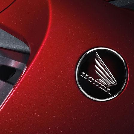 Emblém Honda Wing na červené motocyklové nádrži.