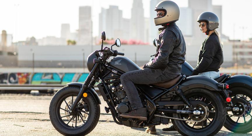 Motocykl Honda CMX500 Rebel z boku s mužem a ženou venku.